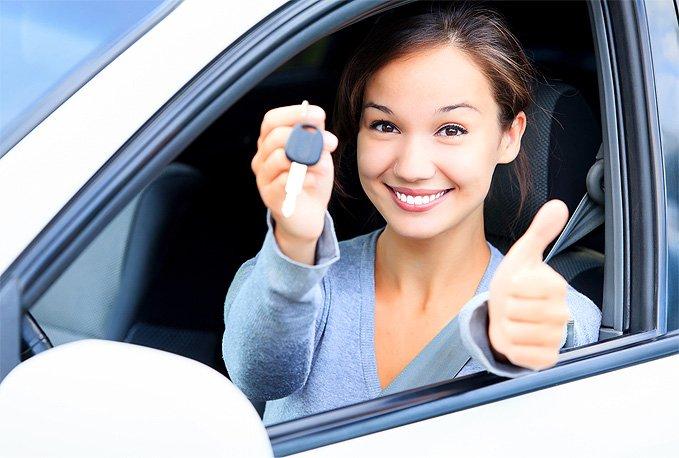 Fahrschülerin hält Autoschlüssel in der Hand und freut sich